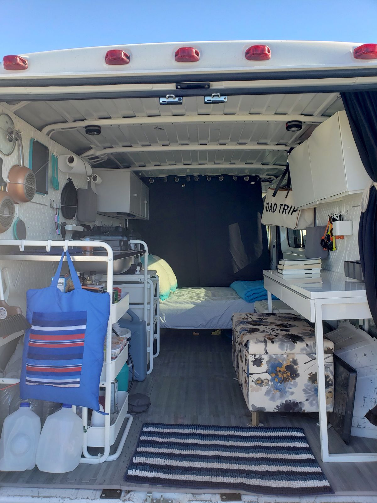 The rear view of a passenger cargo van that's been transformed into a camper. The back doors are open and you can see a desk on the right and a kitchen on the left.