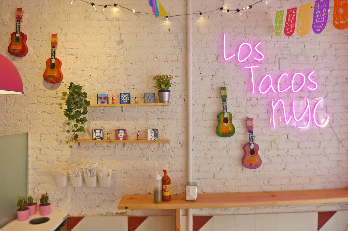A white wall with lots of stuff neatly hung on it, including ukuleles and a neon sign in pink.