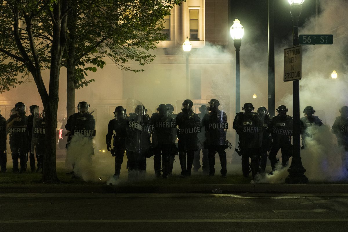 Police advance on protesters in Civic Park through a curtain of smoke, during a protest over the shooting of Jacob Blake, Tuesday, Aug. 25, 2020, in Kenosha, Wis.