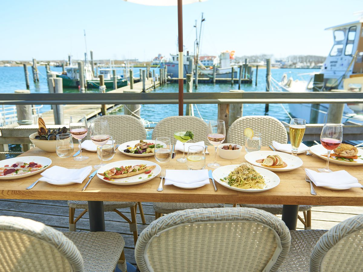 Plates, silverware, and glasses set up on a table with wicker chairs positioned outdoors on a sunny deck overlooking a harbor