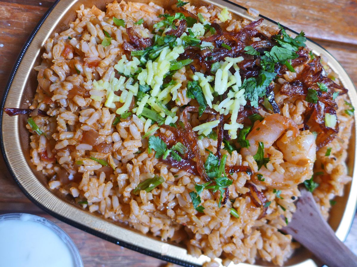A rectangular metal container with dark rice and a shrimp or two visible.