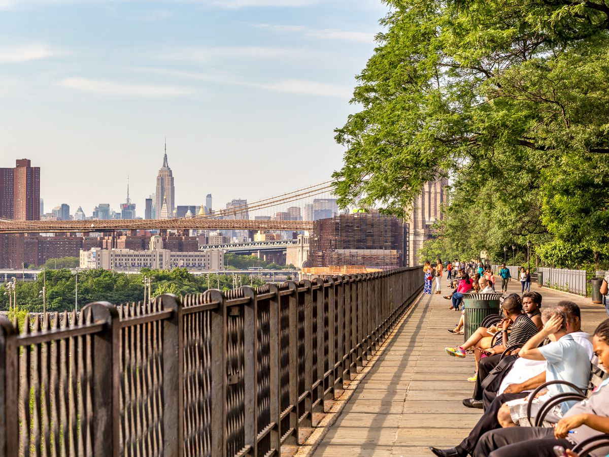 People sit on benches on a walkway with a long, wrought-iron railing. In the distance is a bridge and multiple city skyscrapers.