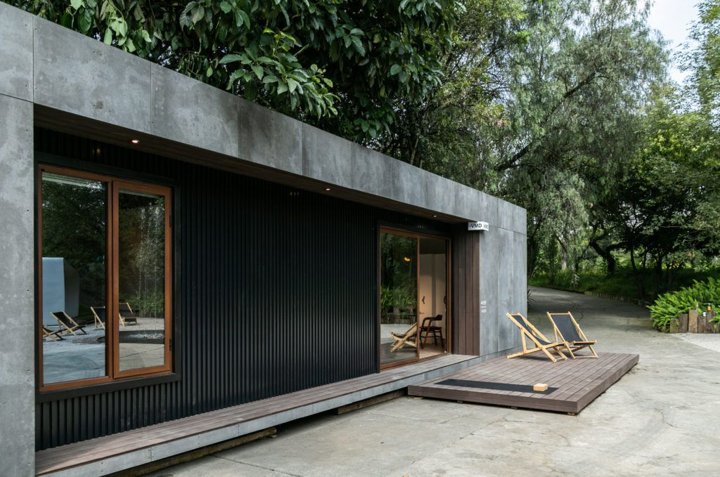 Close up of house with concrete and black metal exterior and a wooden deck.