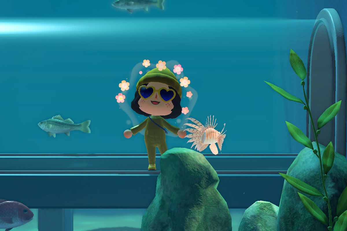 An Animal Crossing human wearing all yellow standing in front of a aquarium tank