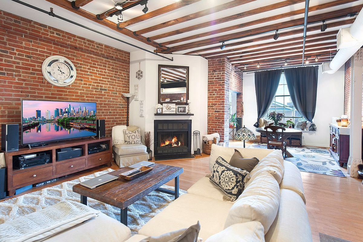 A sunny living room with a fireplace, exposed beams, and exposed brick.