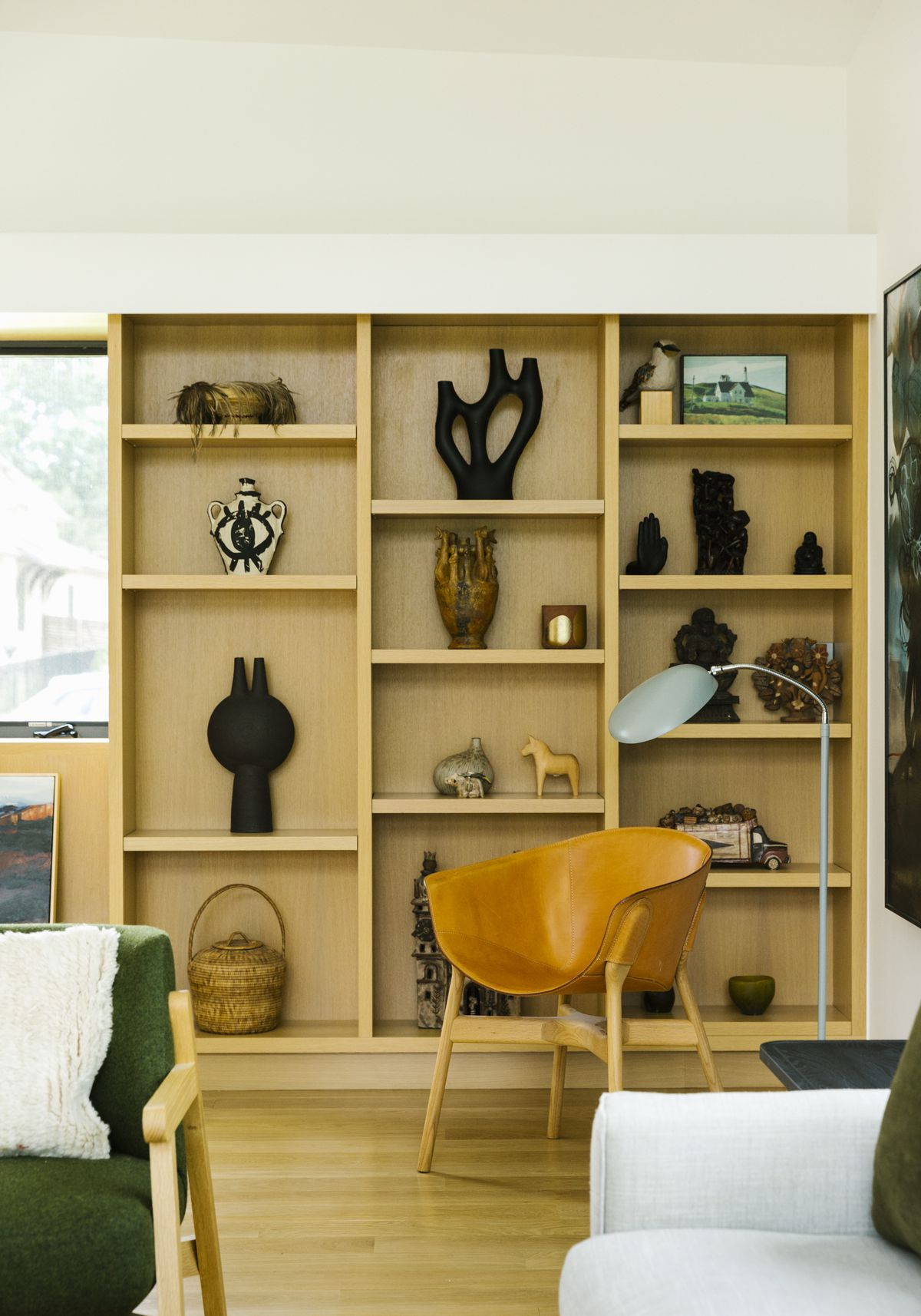 A chair and lamp sit in front of built-in wooden shelves, which are filled with sculptures, art, and other objects.