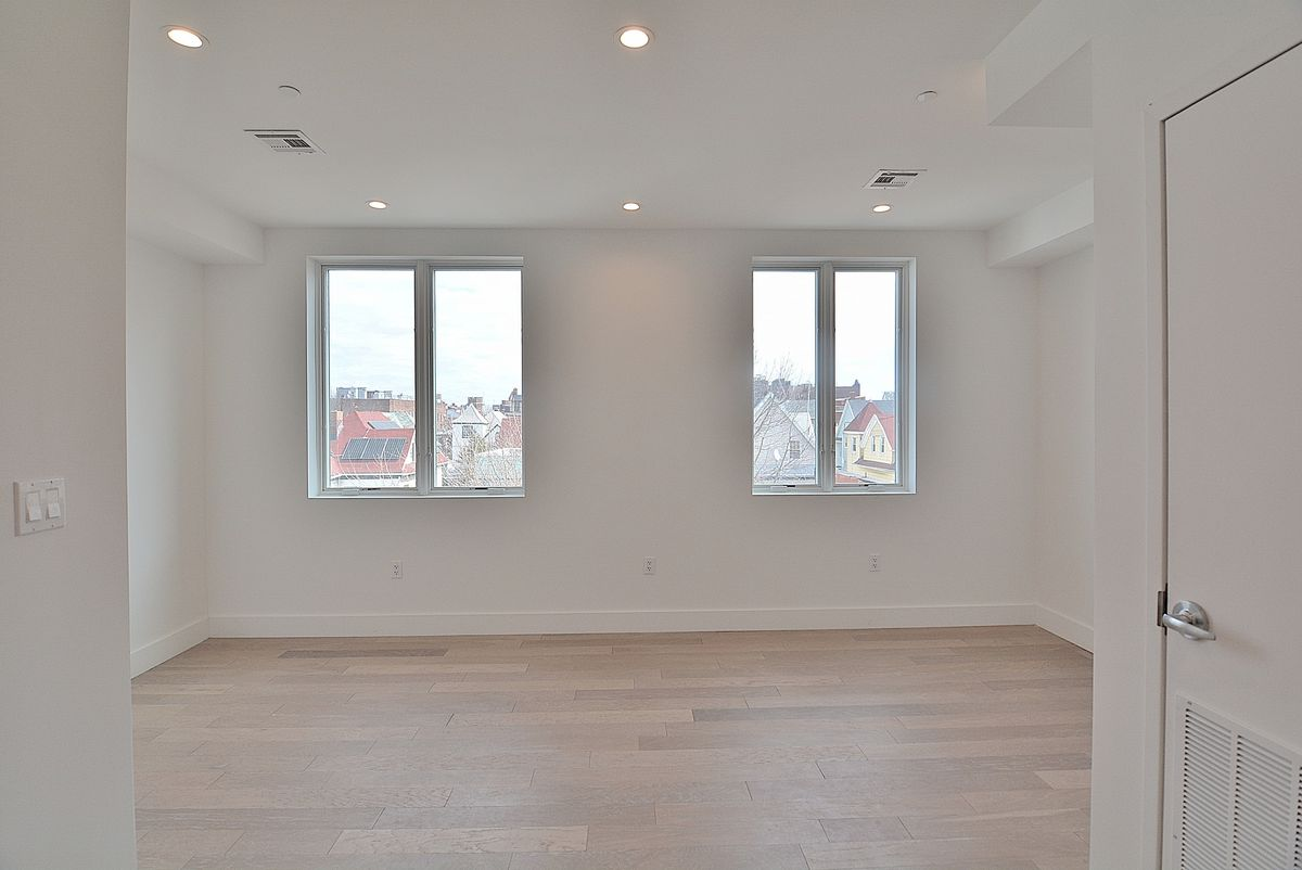 A living area with hardwood floors, white walls, and two windows.