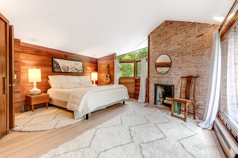 A white bed sits in front of mahogany paneling and a fireplace.