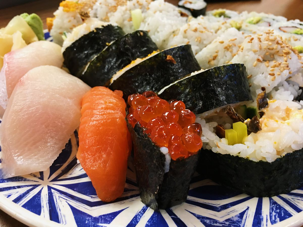 an assortment of nigiri and sushi rolls on a blue and white patterned plate