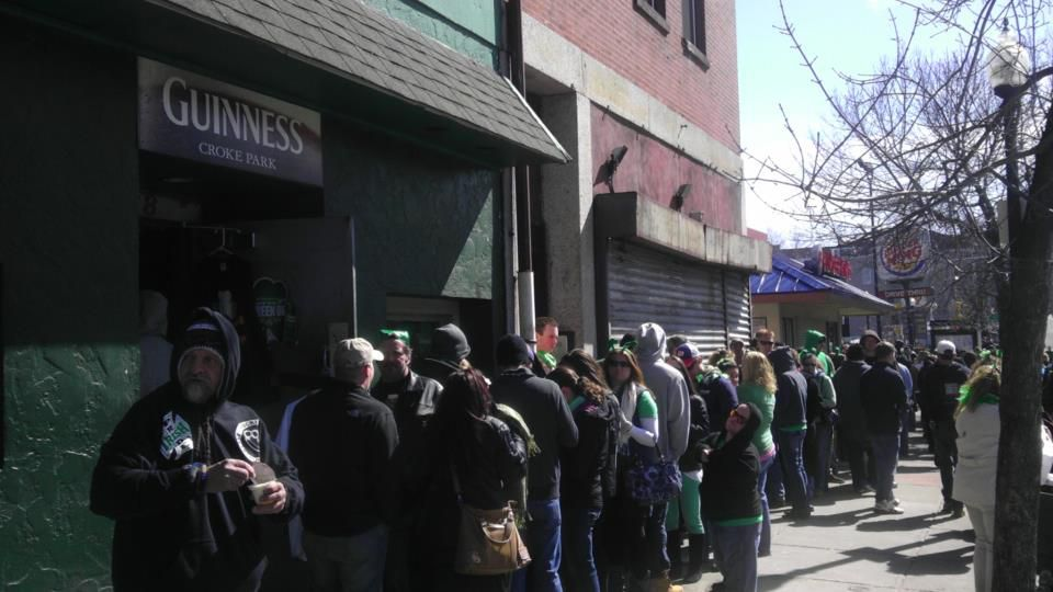 A line of people in green clothing and St. Patrick's Day paraphernalia are lined up down the sidewalk in front of a bar