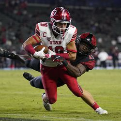 Utah wide receiver Britain Covey (18) runs to the end zone for a touchdown while being tackled by San Diego State safety Cedarious Barfield (27) during the second half of an NCAA college football game Saturday, Sept. 18, 2021, in Carson, Calif.