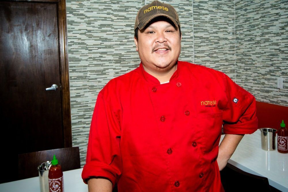 A man stands in a small corner of a kitchen wearing a bright red chef's coat