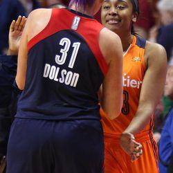 Connecticut Sun's Morgan Tuck (33) shares an embrace with her former Huskies teammate Stefanie Dolson (31).