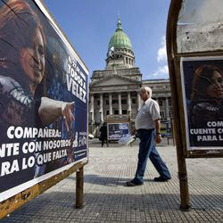 """A sign of Argentina's President Cristina Fernandez that reads in Spanish """"Companion, count on us for what's left"""" covers a bus stop outside Congress where a bill proposed by Fernandez to gain control of Argentina's energy reserves is being discussed in Buenos Aires, Argentina, Tuesday April 17, 2012.  Fernandez pushed forward a bill to renationalize the country's largest oil company on Monday despite fierce criticism from abroad and the risk of a major rift with Spain. Fernandez said the legislation put to congress would give Argentina a majority stake in oil and gas company YPF by taking control of 51 percent of its shares currently held by Spain's Repsol."""