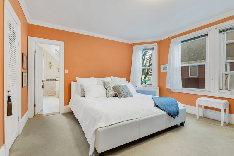 A bedroom with orange walls and several windows.