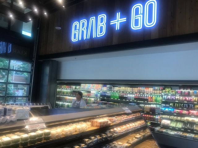 """A view of the """"Grab and Go"""" section, displaying beverages and shelves of food."""