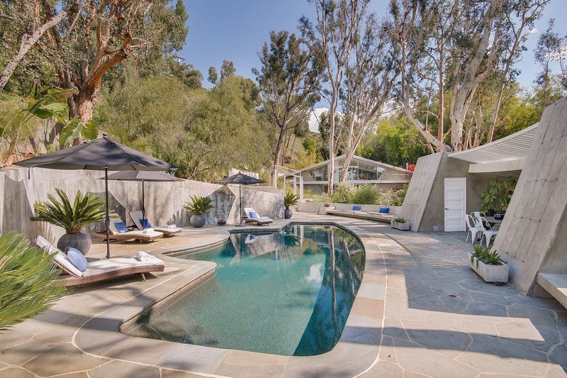 A gray stone pool area with large umbrellas and lounge chairs.