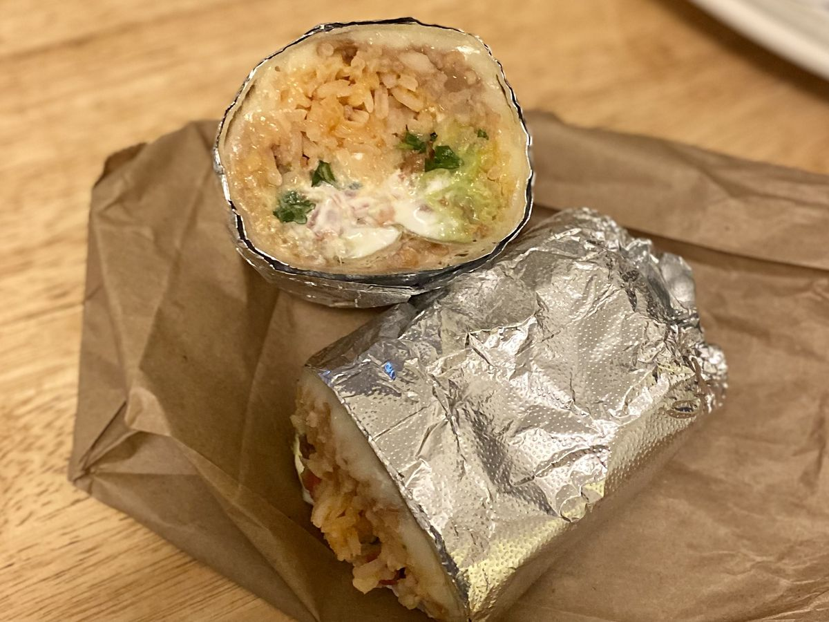 A bean and cheese burrito wrapped in foil and cut in half.