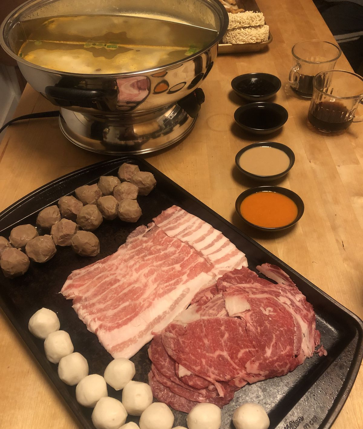 A hot pot with broth is visible in the background and a dark platter with fish and beef balls plus sliced red meats is set in front of the hot pot. Four sauces in small dark bowls are set alongside the other items on a light wooden table.