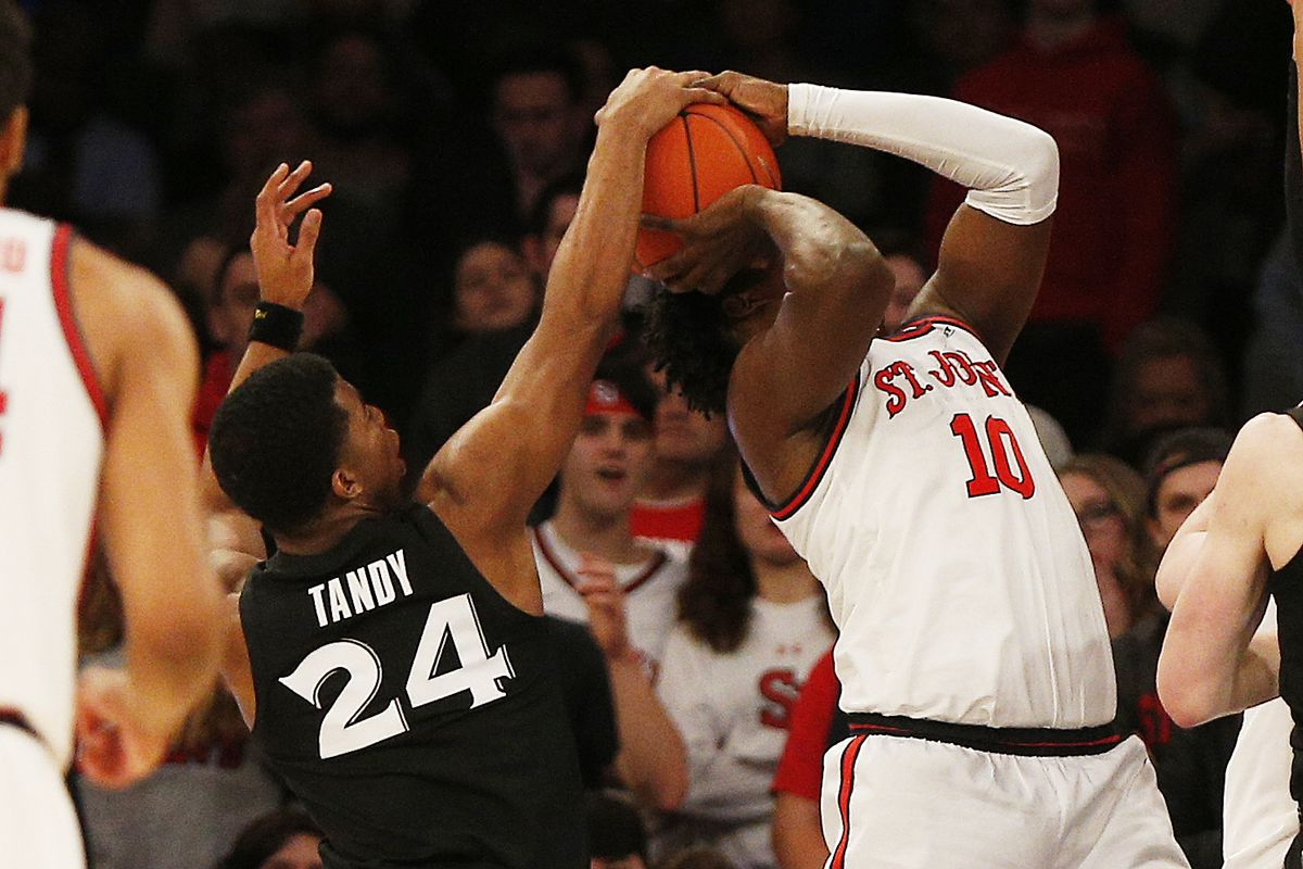 St. John's Red Storm forward Marcellus Earlington and Xavier Musketeers guard KyKy Tandy fight for the ball during the first half at Madison Square Garden.