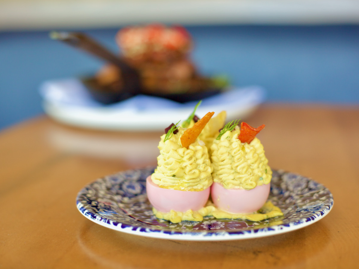 Two very high deviled eggs, the whites dyed pink, on a decorative plate with a large meat dish blurred in the background
