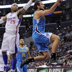 New Orleans Hornets guard Marco Belinelli, right, of Italy, goes up for a shot as Los Angeles Clippers guard Mo Williams defends during the first half of their NBA basketball game, Sunday, April 22, 2012, in Los Angeles.