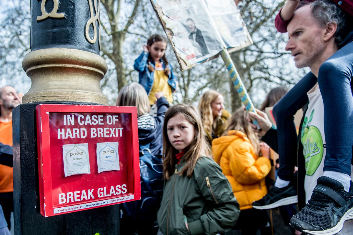 "Protesters pass a mock emergency box containing tea bags that reads ""In Case of Hard Brexit Break Glass"" during the People's Vote anti-Brexit march in London on March 23, 2019."