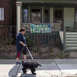 A woman walks her dog past a sign thanking helpers hanging on a home in the 3000 block of West Wilson Avenue in the Irving Park neighborhood, Tuesday, April 7, 2020.