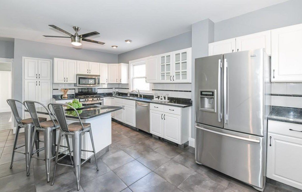 A modern kitchen with a large, double-door fridge and a stylish island with chairs.