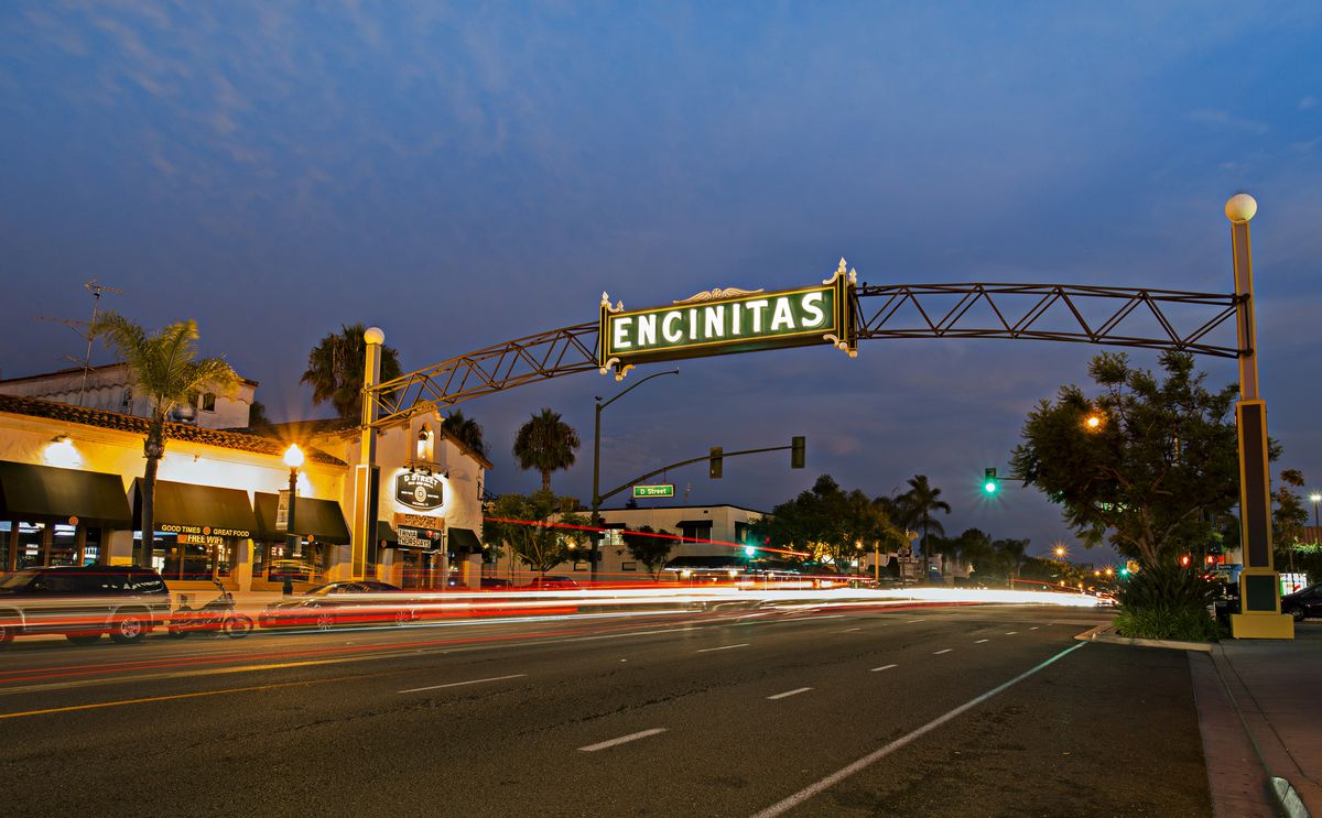 Encinitas sign with lights from cars whizzing by at twilight.