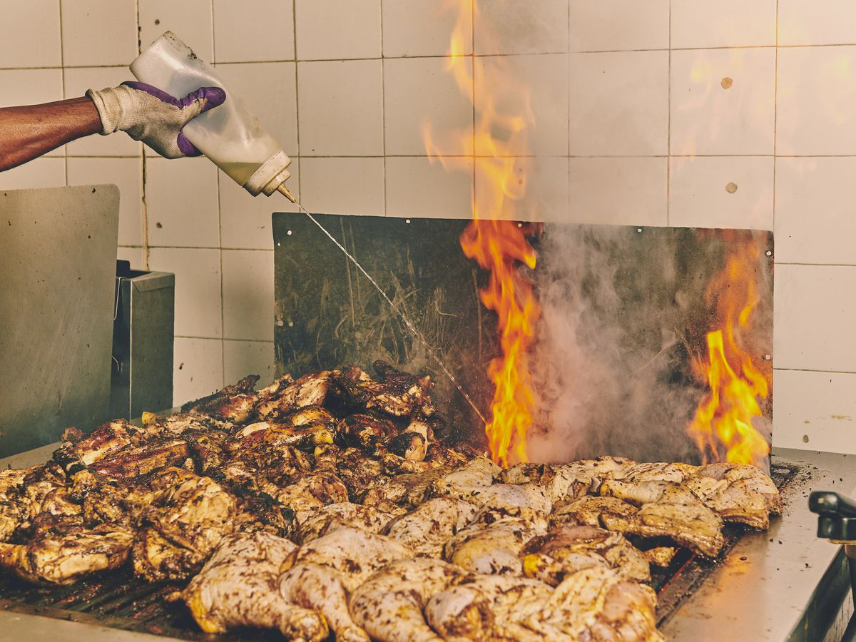 Many cuts of jerk chicken laid on the grill with flames shooting up and a hand squeezing sauce over top of the chicken