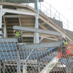 Girder being positioned into the patio, behind the scoreboard -