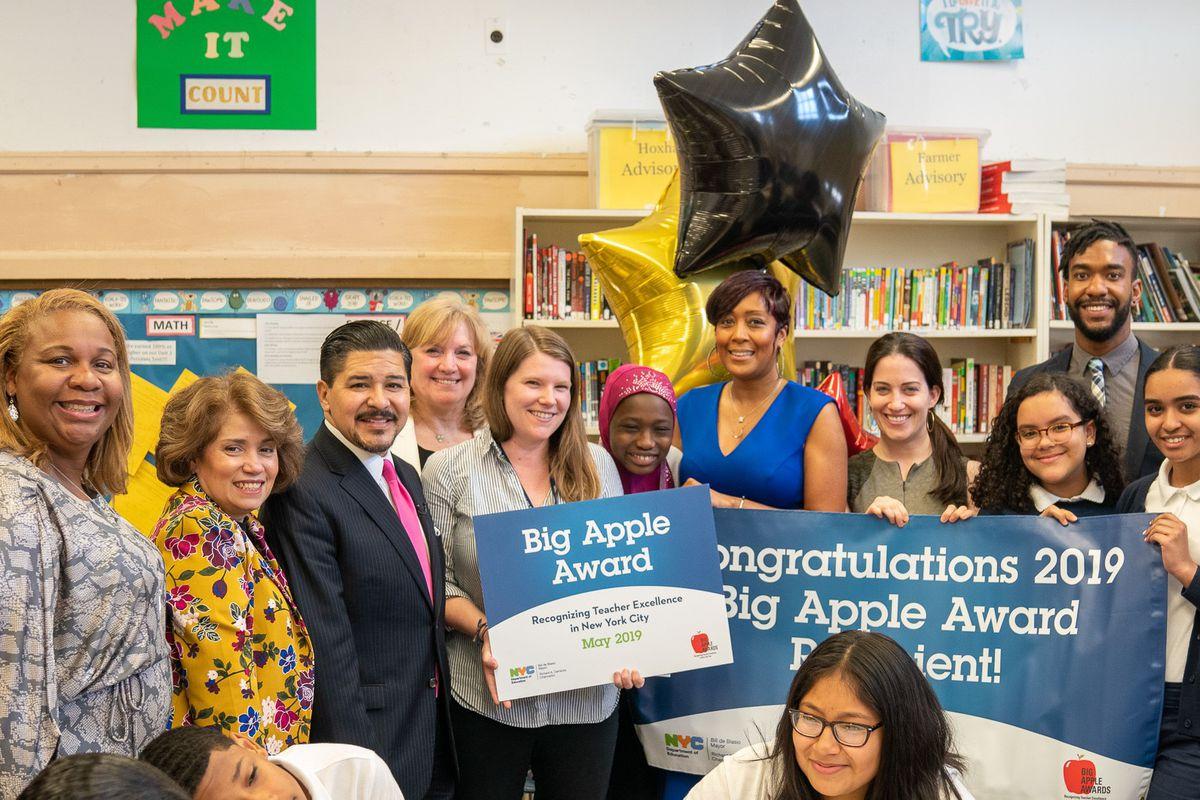 Chancellor Carranza delivers a 'Big Apple' award to Emilie Jones-McAdams, an English teacher at I.S. 303 in the Bronx.