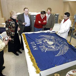 Flag historians, enthusiasts and curators from the state Capitol, Fort Douglas Museum and an LDS Church history representative gather around Utah's first state flag.