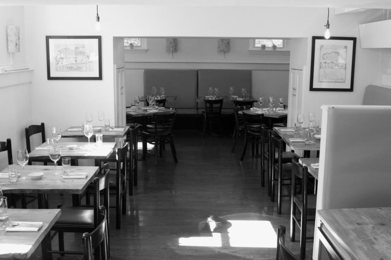 A black-and-white interior photo of a small, empty restaurant