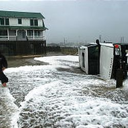 Chris Scarborough, 23, checks out an SUV flipped by the waves along N.C. 12 in Kitty Hawk, N.C., Thursday. Isabel was blamed for at least four traffic deaths.