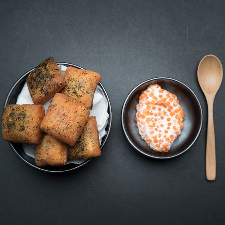 From above, a plate of puffed square donuts topped with herb salt, beside a bowl of cream dotted with roe, and a wooden spoon on a dark surface