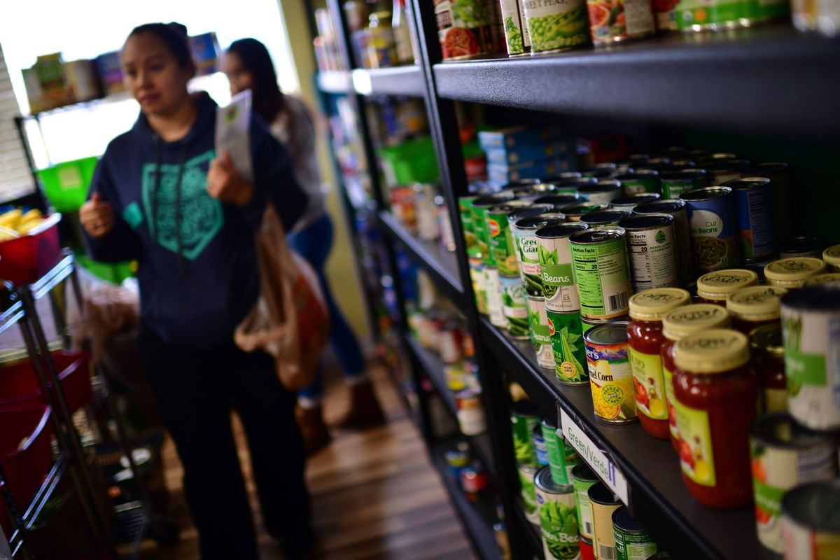 A woman peruses the aisles of a food bank; cans and jars line the shelves.