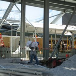 3:45 p.m. Worker carrying away a packed section of the temporary batting cage tent -