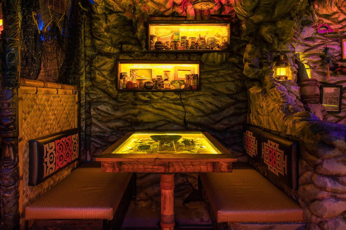 At a booth set in a faux-grotto, the glass-top table displays ephemera, and two yellow-lit wall compartments display mugs.