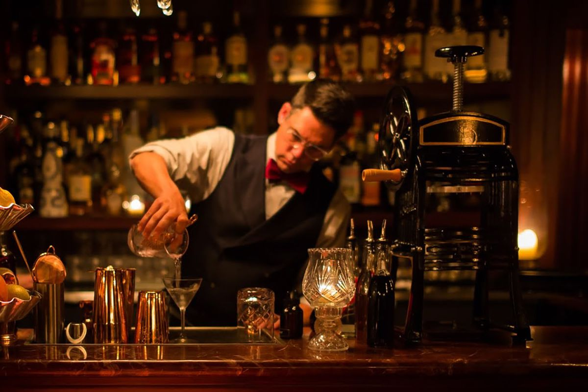 A bartender with a throwback vest and red bowtie pours a martini from behind a vintage bar.