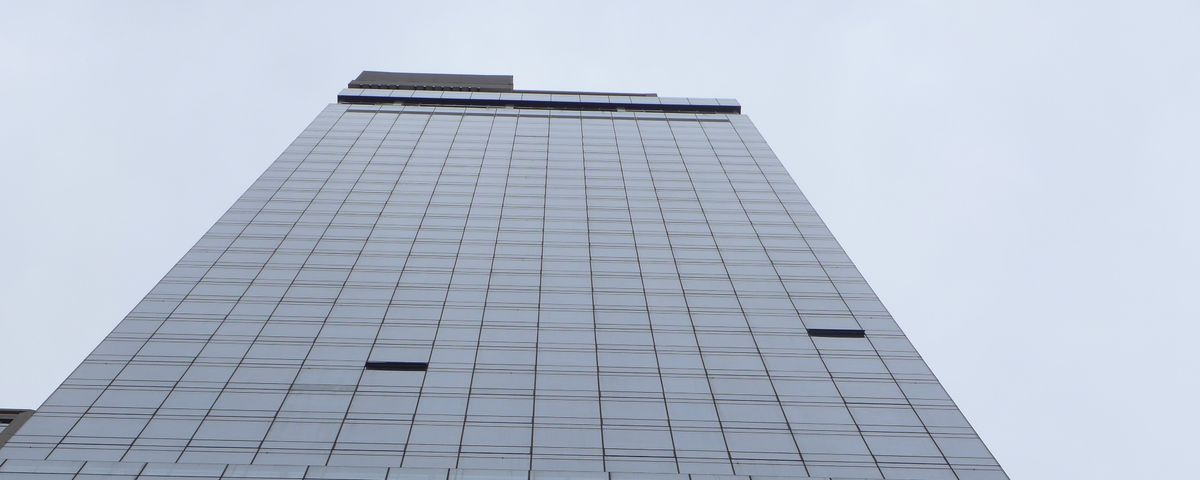 A tall, dark-windowed building stands against a gray sky