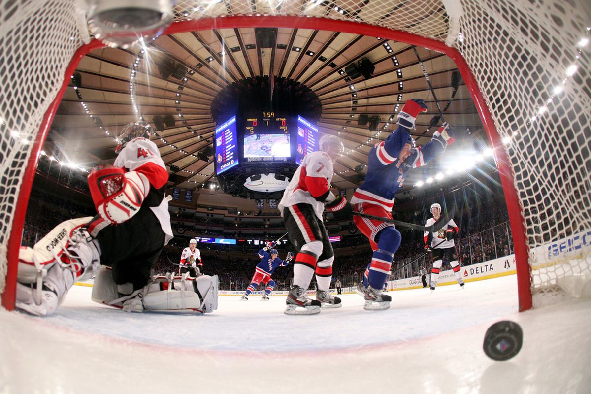 Craig Anderson complains to the referee about the novelty goal posts that bend outwards when the Rangers shoot the puck.