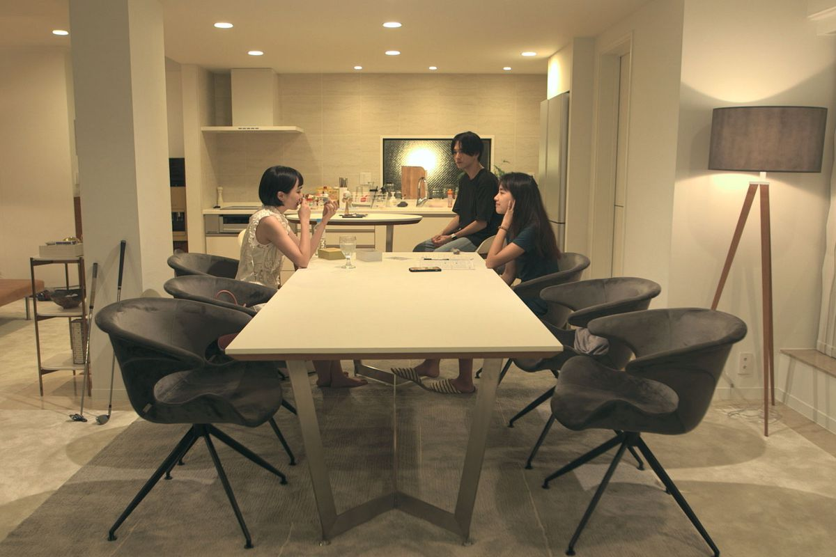 A still from Terrace House Tokyo 2019 2020. In the foreground, three people sit around a large white table which is flanked by dark grey chairs. There is a grey area rug under the table. In the background there is a kitchen. The walls are white.