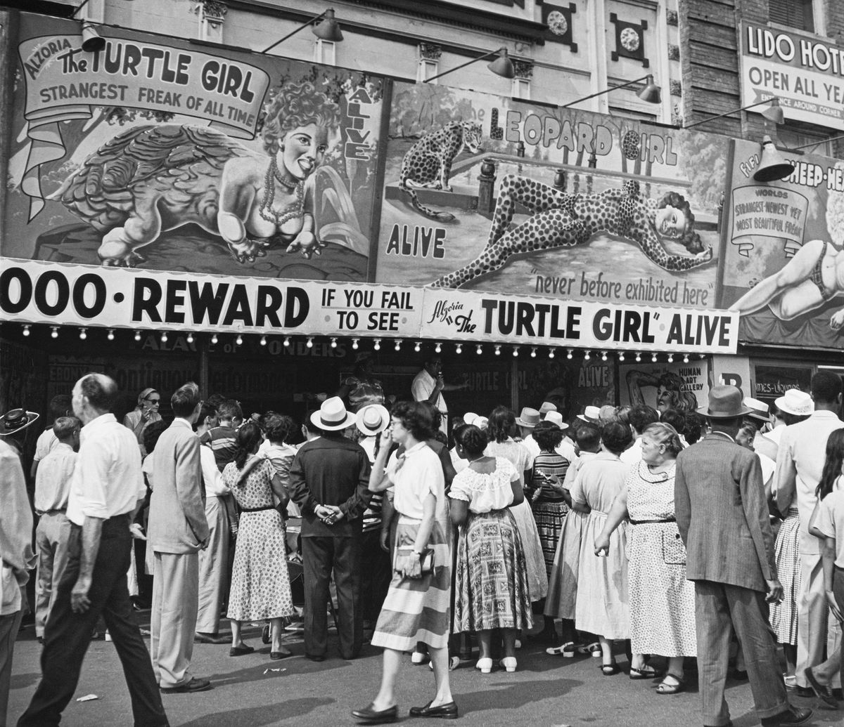 """In a circa 1945 photograph, people wait outside a freak show to see """"The Turtle Girl"""" and """"The Leopard Girl."""" A sign adds, """"Reward if you fail to see 'The Turtle Girl' alive."""""""
