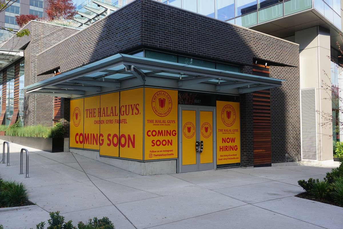 """An exterior look at the yellow """"coming soon"""" signage for Halal Guys on a brick building in South Lake Union."""