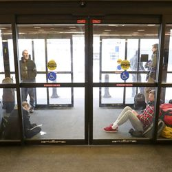 Airline passengers wait between the exit doors at the Salt Lake City International Airport after a 5.7 magnitude earthquake centered in Magna caused the airport to be evacuated and closed on Wednesday, March 18, 2020.