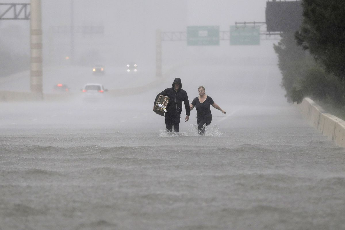 Two people walk down a flooded section of Interstate 610 in floodwaters from Tropical Storm Harvey on Sunday, Aug. 27, 2017, in Houston, Texas.