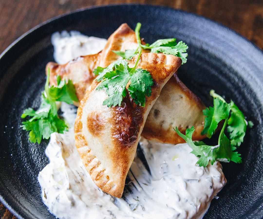 Three small golden-brown empanadas are stacked on top of each other on a white creamy sauce, garnished with parsley, on a shiny black plate.