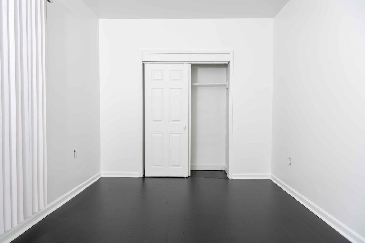 Empty room with white walls and a sliding door in front of a closet.